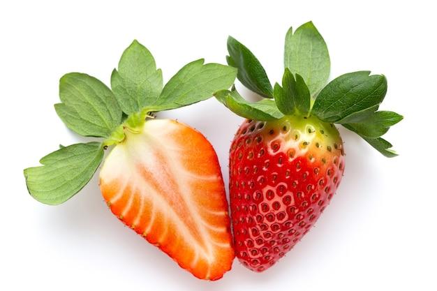 Isolierte erdbeeren. zwei ganze erdbeerfrüchte und die hälfte isoliert auf weißer oberfläche.