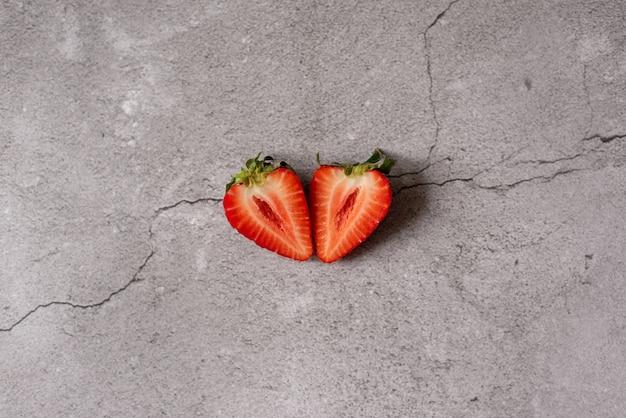 Isolierte erdbeeren. zwei herzförmige erdbeerfrüchte halbieren