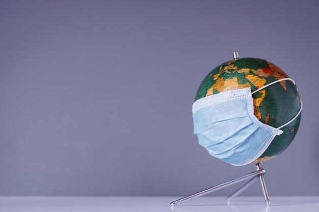 Isolierte erdkugel mit gesichtsmaskenschutz mit platz für text. reisen weltweit und coronavirus medizinisches konzept.