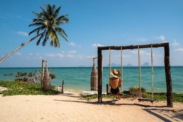 Isolierte frau auf ihrem romantischen flitterwochenurlaub an einem paradiesischen strand mit palmen. teures luxusresort für verheiratete paare und alleinstehende. entspannen sie sich auf einer schaukel. reise nach thailand konzept.