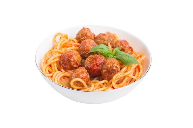 Isolierte frikadellen spaghetti. traditionelle gerichtsspaghetti mit fleischbällchen, tomatensauce und frischem basilikum in der weißen schüssel, lokalisiert auf weißem hintergrund