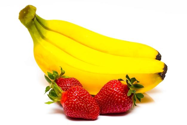 Isolierte früchte. bündel von bananen und haufen von erdbeeren lokalisiert auf weißem hintergrund