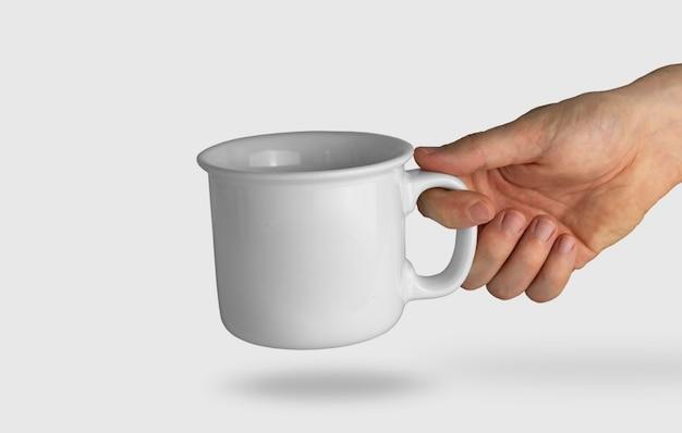 Isolierte hand, die einen weißen becher hält