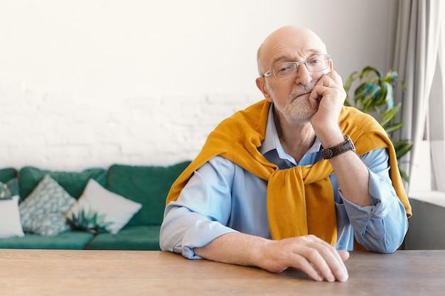 Isolierte innenaufnahme des attraktiven eleganten sechzigjährigen rentners mit weißem bart und kahlem kopf, der am holztisch im wohnzimmer sitzt, gelangweilt ist, hand am kinn hält und nachdenklichen blick hat
