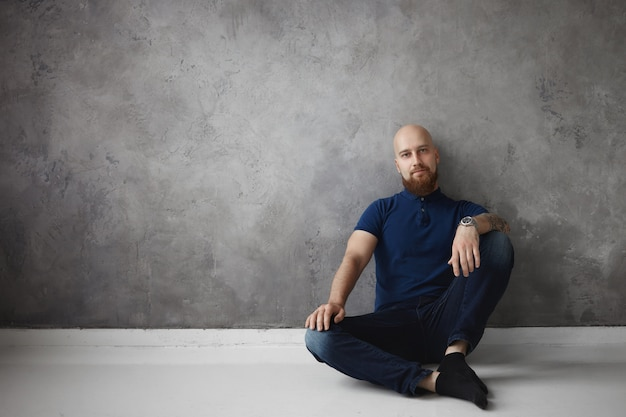 Isolierte innenaufnahme des attraktiven kahlen mannes im stilvollen poloshirt, in den jeans und in den socken, die zu hause entspannen, bequem auf boden mit hand auf seinem knie sitzen, ruhe nach hartem arbeitstag im büro haben
