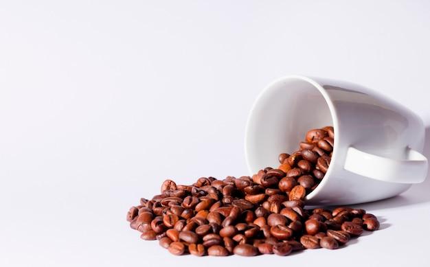 Isolierte kaffeebohnen mit keramikbecher, weißer tisch.