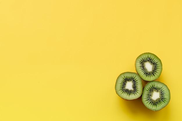 Isolierte kiwi. eine kiwi schnitt zur hälfte, die auf gelbem hintergrund mit beschneidungspfad lokalisiert wurde