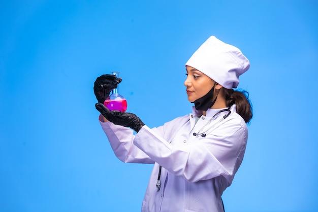 Isolierte krankenschwester in der hand und gesichtsmaske hält chemischen kolben.