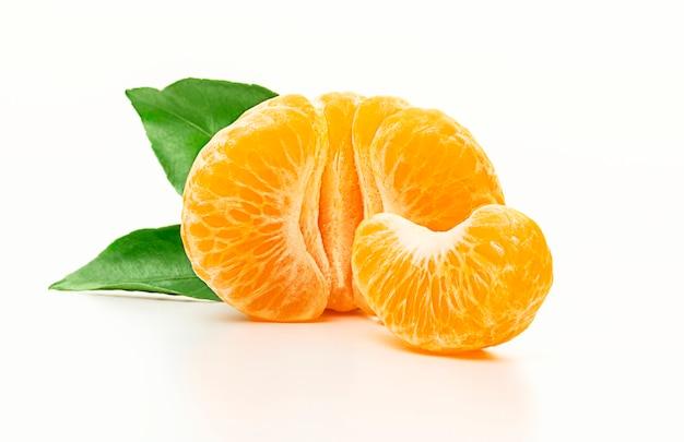 Isolierte mandarine. die hälfte der geschälten mandarine oder der orangenfrucht mit den blättern lokalisiert auf weißem hintergrund. nahansicht.