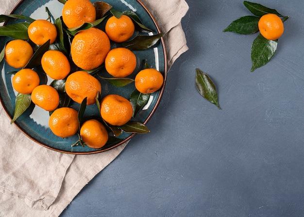 Isolierte mandarine (mandarine) auf schwarzem hintergrund. frische mandarinen zitrus. clementinenfrucht mit grünem blatt, gesundes leckeres bio-lebensmittel, weihnachtspflanze