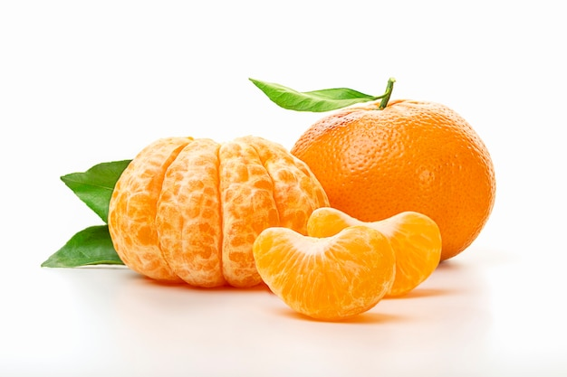 Isolierte mandarinen. die hälfte der geschälten mandarine und der ganzen mandarine oder der orangenfrucht mit den grünen blättern lokalisiert auf weißem hintergrund. nahansicht.