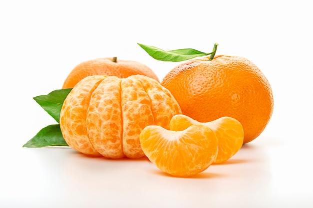 Isolierte mandarinen. die hälfte der geschälten mandarine und der ganzen mandarine oder der orangenfrucht mit den grünen blättern lokalisiert auf weißem hintergrund