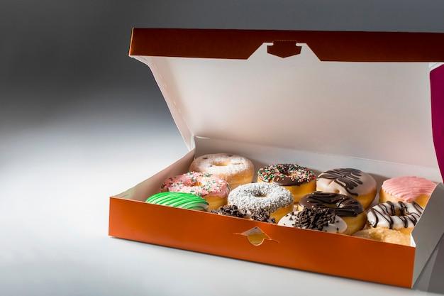 Isolierte orange box mit sortierten donuts auf neutralem hintergrund