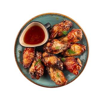 Isolierte platte der pikanten hühnerflügel-vorspeise mit soße
