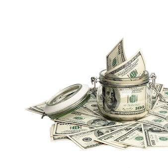 Isolierte rechnungen von einhundert us-dollar. geld ist auf einem weißen hintergrund um ein glas dollar verstreut.