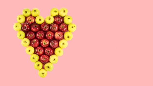 Isolierte rote und gelbe äpfel, die ein herz auf rosa bilden