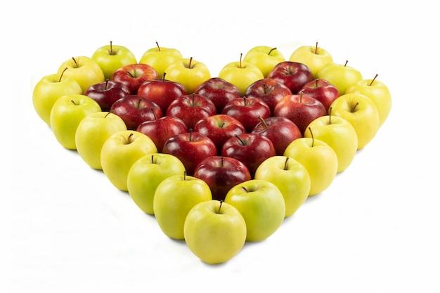 Isolierte rote und gelbe äpfel, die ein herz auf weiß bilden
