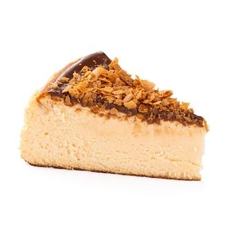 Isolierte scheibe spanischen käsekuchens mit geschmolzener schokolade auf der weißen oberfläche