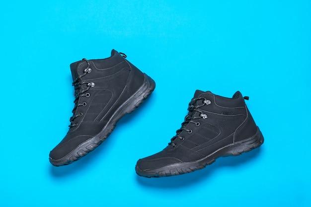 Isolierte schwarze sport herrenschuhe auf hellblauer oberfläche. herrenschuhe für kaltes wetter. flach liegen.