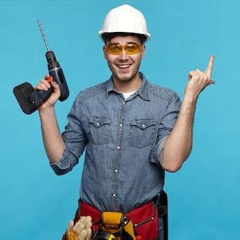 Isolierte studioaufnahme des fröhlichen emotionalen jungen reparaturmanns, der schutzbrille trägt