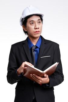 Isolierte studioaufnahme eines asiatischen, selbstbewussten, erfolgreichen männlichen vorarbeiter-wirtschaftsingenieurs in schwarzem anzug und schutzhelm, der die überwachung der arbeit vom notebook auf weißem hintergrund liest.