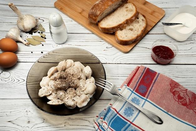 Isolierte traditionelle russische pelmeni-ravioli-knödel mit fleisch auf holzhintergrund