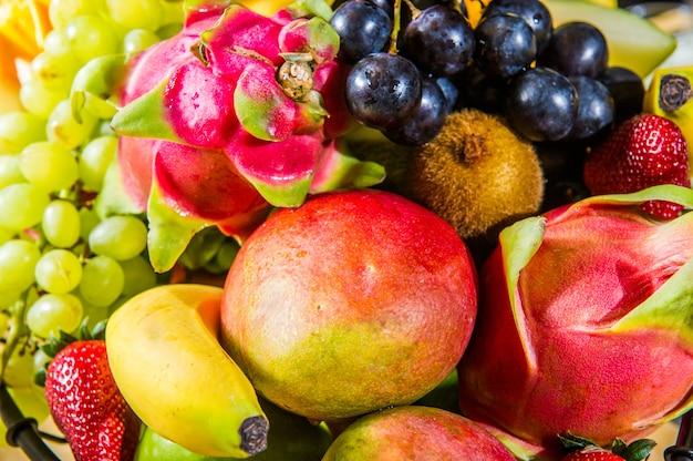 Isolierte tropische fruchtscheiben. frische exotische früchte halbiert (maracuya, kiwi, mangostan, ananas, drachenfrucht) in folge einzeln auf weißem hintergrund mit beschneidungspfad