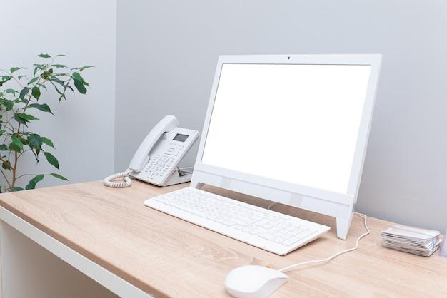 Isolierte weiße computeranzeige für modell auf schreibtisch in hellem gemütlichem büro mit weißer computermaus