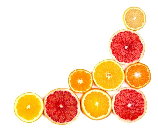 Isolierte zitrusfrüchte. stücke von zitrone, limette, rosa grapefruit und orange lokalisiert auf weißem raum, mit beschneidungspfad. draufsicht