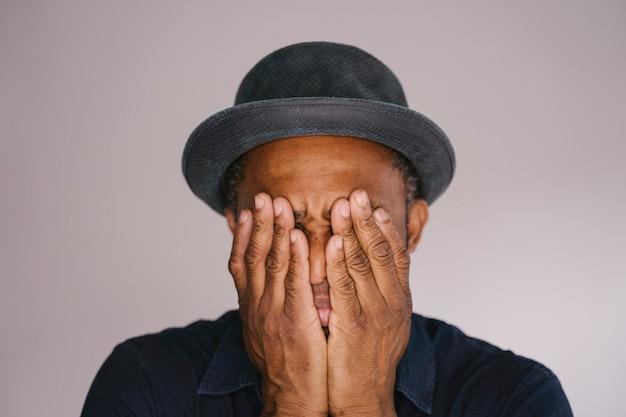 Isolierter afroamerikanermann, der sein gesicht mit händen bedeckt. symptome von depressionen und traurigkeit.