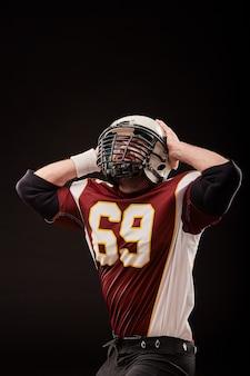 Isolierter american-football-spieler freut sich über den sieg im schwarzen hintergrund