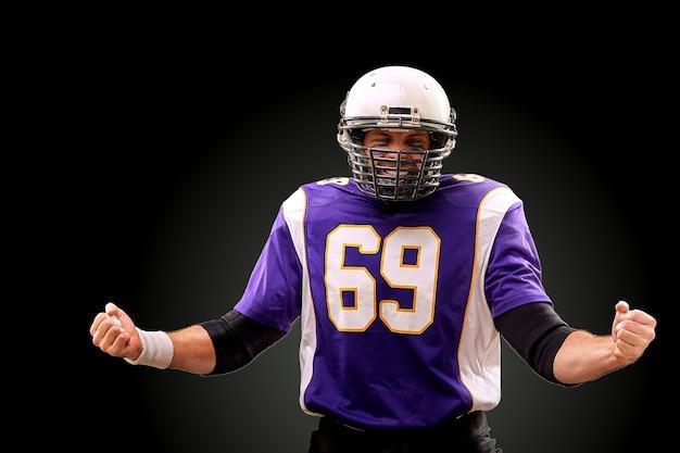 Isolierter american-football-spieler freut sich über den sieg in der schwarzen wand