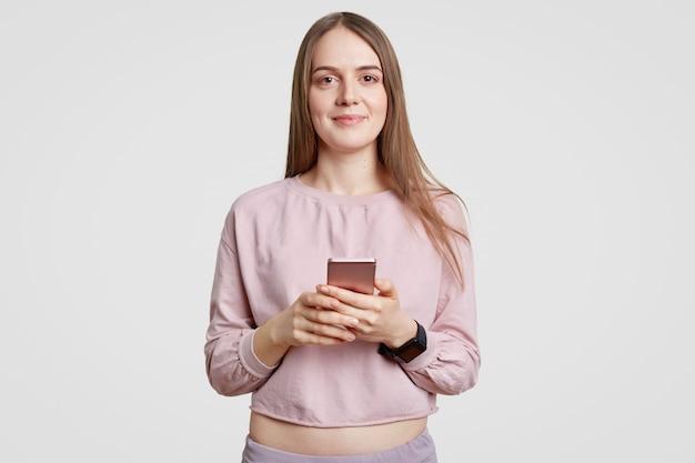 Isolierter ansprechender teenager mit angenehmem aussehen, hält handy, schreibt textnachrichten, trägt freizeitkleidung und ist mit dem drahtlosen internet verbunden. menschen- und technologiekonzept
