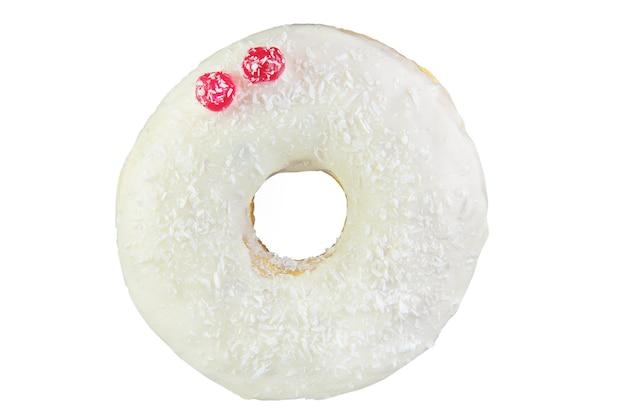 Isolierter donut mit kokoschips, roten beeren und weißer zuckerglasur schoss in einen stapel. durch stapeln fotografiert.