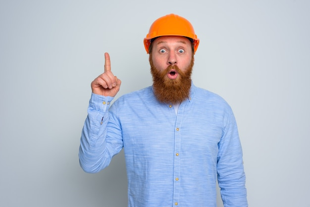 Isolierter erstaunter architekt mit bart und orangefarbenem helm
