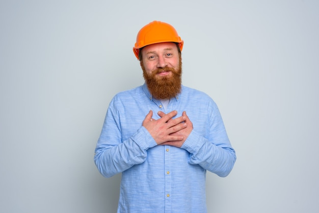 Isolierter glücklicher architekt mit bart und orangefarbenem helm