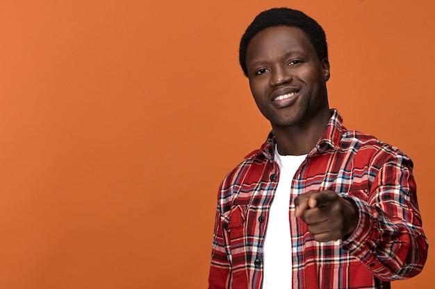 Isolierter hübscher fröhlicher junger dunkelhäutiger schwarzer mann, der stilvolles kariertes hemd trägt, breit lächelt und seinen vorderfinger zeigt, als ob er sie wählt. selektiver fokus