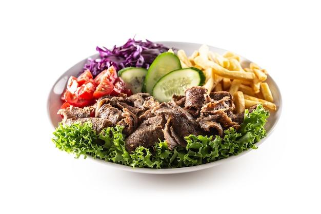 Isolierter köstlicher türkischer kalbskebab serviert auf dem weißen teller mit frischem grünem salat, saftigen tomaten, kohl, gurken und knusprigen und salzigen pommes frites.