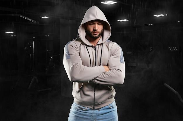 Isolierter muskulöser mann auf einem schwarzen fitnessstudio in einem sweatshirt