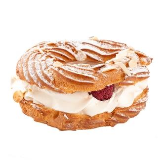 Isolierter paris-brest-kuchen mit sahne und himbeere auf der weißen oberfläche