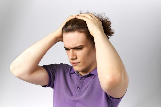 Isolierter schuss des gestressten verärgerten jungen geschäftsmannes im lässigen poloshirt, der stirnrunzeln händchen haltend auf seinem kopf runzelt, frustrierten blick wegen problemen. stress, depression und frustration konzept