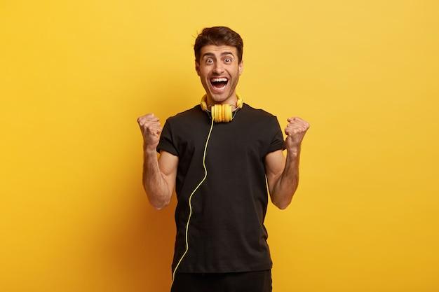 Isolierter schuss des glücklichen triumphierenden tausendjährigen mannes hebt geballte fäuste