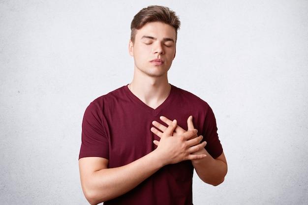 Isolierter schuss eines erfreuten dankbaren mannes mit starkem körper