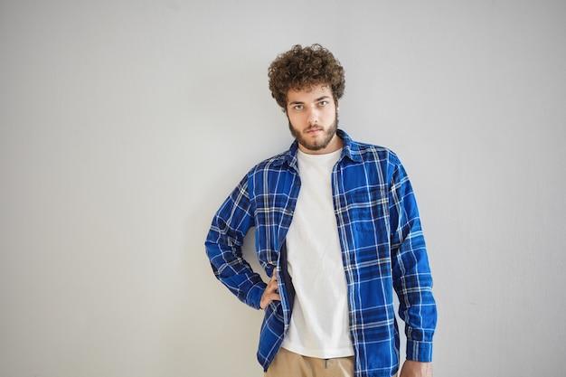 Isolierter stilvoller ernster junger mann mit dickem bart und welligem haar mit selbstbewusstem blick, hand auf seiner taille haltend. konzept für menschen, stil, mode und herrenbekleidung