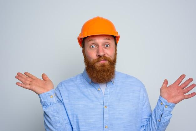 Isolierter unsicherer architekt mit bart und orangefarbenem helm
