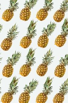Isoliertes ananasmuster oder tapete auf weißem hintergrund. sommerkonzept von frischen reifen ganzen ananas von oben geschossen