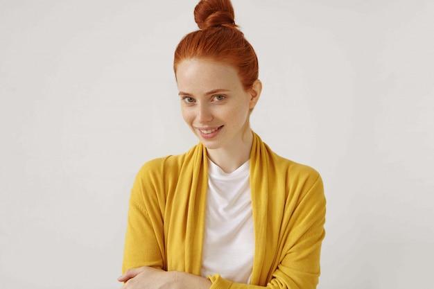 Isoliertes bild der attraktiven rothaarigen sommersprossigen jungen frau mit dem haarbrötchen, das geheimnisvoll lächelt und glücklichen ausdruck auf ihrem gesicht hat. positive menschliche emotionen, gefühle, einstellungen und reaktionen