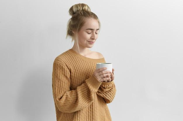 Isoliertes bild der herrlichen bezaubernden jungen frau mit haarknoten, die großen becher hält, der frisch gemachten cappuccino vom großen becher genießt, gemütlichen übergroßen pullover trägt, augen geschlossen hält und lächelt