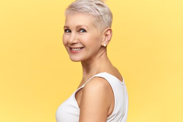 Isoliertes bild der herrlichen charmanten frau mittleren alters mit gefärbtem kurzem haar, das den kopf dreht, glücklich lächelnd, gegen leeren gelben hintergrund mit kopienraum posierend