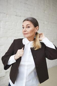 Isoliertes bild der modischen attraktiven reifen europäischen frau, die stilvolle jacke über weißem formellem hemd trägt und sich für die arbeit am morgen fertig macht